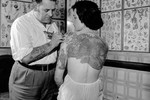 Pam Nash, a champion tattooed lady, with a Japanese garden scene across her back, 1960s.