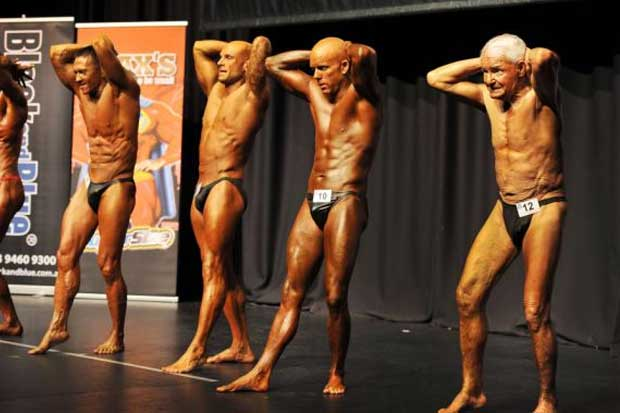 Raymond flexes his muscles alongside fellow competitors less than half his age.