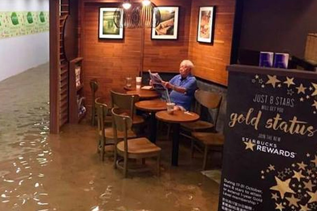 Man ignores the flooding happening around him and continues to read his paper